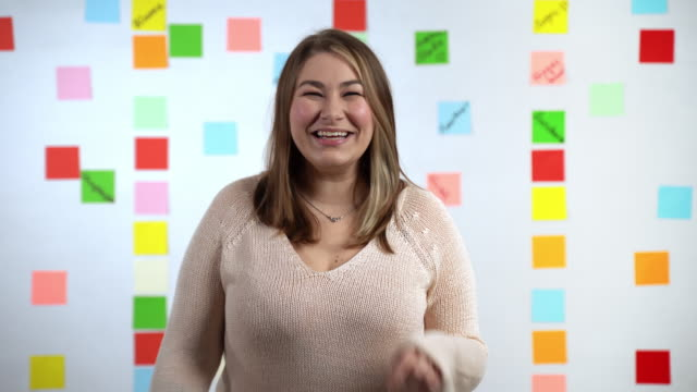 Pretty smiling girl with overweight looking at camera and posing on colorful background. Brunette woman in casual clothes showing happiness emotions, joy and fortune. Positive facial expressions and successful people