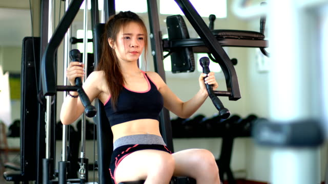 Pretty sport girl working out on chest press machine video