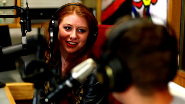 Pretty student interviewing someone for radio in the studio video