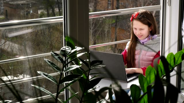 pretty teenager girl is typing, working on laptop, on open balcony. spring sunny day. Concept of distance learning during quarantine. stay, study at home. coronavirus epidemic - vídeo