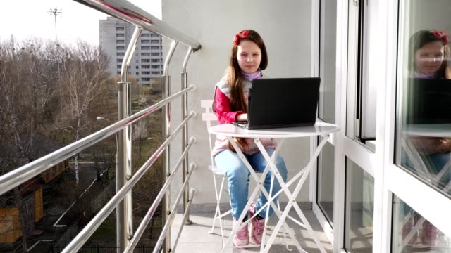 pretty teenager girl is typing, working on laptop, on open balcony. spring sunny day. concept of distance learning during quarantine. stay, study at home. coronavirus epidemic - taras rolny filmów i materiałów b-roll