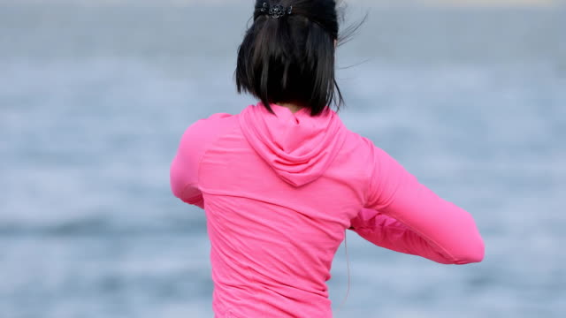 Pretty vigorous sportswoman in pink sportswear warming up before workout outdoors, healthy lifestyle concept video
