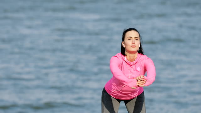 Pretty vigorous sportswoman in pink sportswear warming up before workout outdoors, healthy lifestyle concept Pretty vigorous sportswoman in pink sportswear warming up before workout outdoors, healthy lifestyle concept saturated color stock videos & royalty-free footage