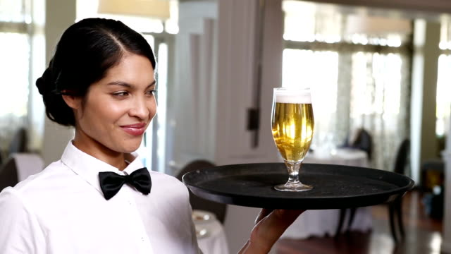Pretty waitress holding tray with glass of beer video