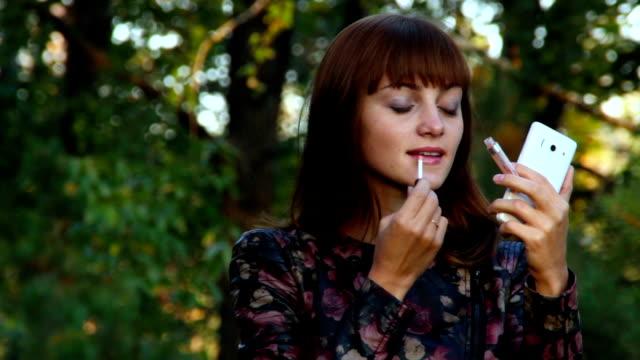 stockvideo's en b-roll-footage met mooie vrouw lipgloss kijken naar de smartphone toe te passen - lipbalsem