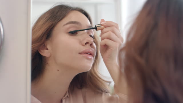 vídeos de stock e filmes b-roll de pretty woman applying mascara with brush on eyelashes in bathroom mirror - rímel