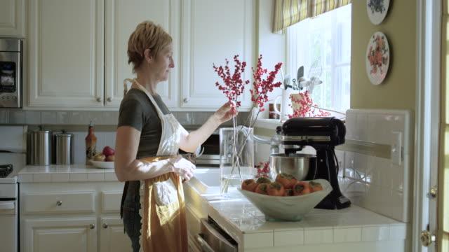 vídeos de stock e filmes b-roll de pretty woman arranging flowers in the kitchen - arranjo