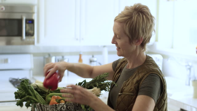Pretty Woman Bringing in the Groceries Beautiful woman brings in the environmentally friendly grocery bag filled with vegetables. She walks in, sets down the bag and unloads the bell pepper, celery, leeks, rosemary onto the kitchen counter. mature women stock videos & royalty-free footage