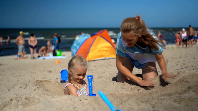 Pretty woman bury little girl with sand on beach. Blurred people holidaymakers