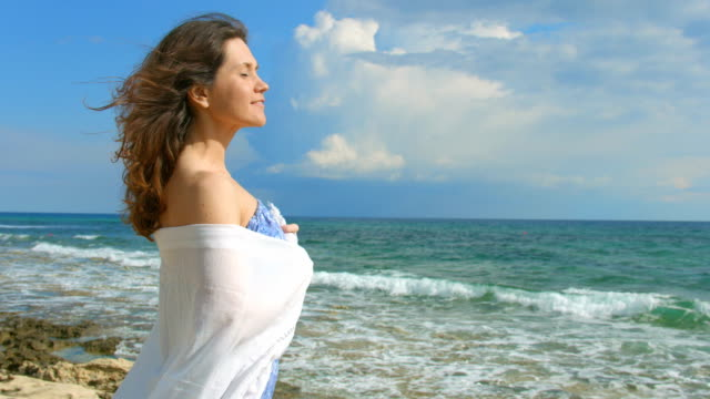 Pretty woman dreaming on the beach, beautiful ocean waves coming video
