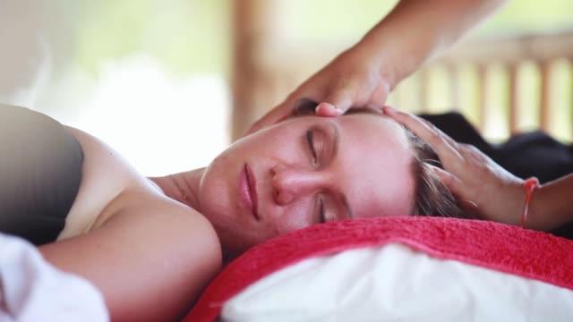 pretty woman getting facial massage in tropical beauty spa. 1920x1080 - kosmetyczka praca w salonie piękności filmów i materiałów b-roll