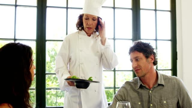 ładna kobieta, dając jej szefa kuchni danie z tyłu - 40 49 lat filmów i materiałów b-roll