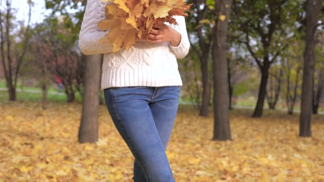Pretty Woman Holding A Bouquet Of Fallen Golden Leaves Outdoors In Autumn Park video