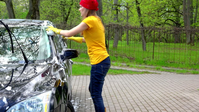 Pretty woman in colorful clothes washing black automobile car with soapy sponge. video