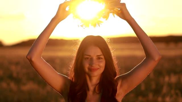 Pretty woman in flower wreath in field at sunset video