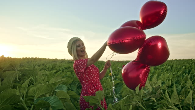 pretty woman in retro red dress posing with heart-shaped balloons in green field. girl in straw vintage hat or beret. birthday, holiday, celebrate freedom concept. - {{asset.href}} video stock e b–roll