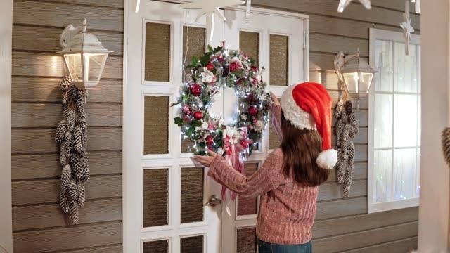 vídeos y material grabado en eventos de stock de bonita mujer con sombrero de santa colgante guirnalda de la navidad en puerta blanca en casa - ornamentado