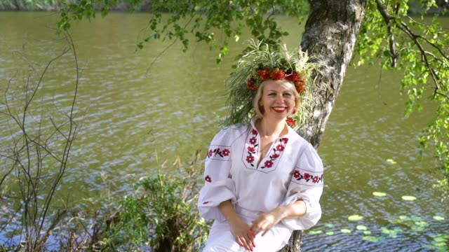 pretty woman in slavic traditional costume lying on trunk of birch tree - славянская культура стоковые видео и кадры b-roll
