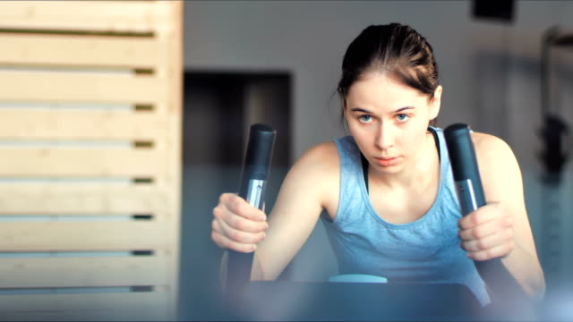 彼女の足は、自転車で有酸素運動トレーニングを行うことを運動ジムできれいな女性 - 女性選手点の映像素材/bロール