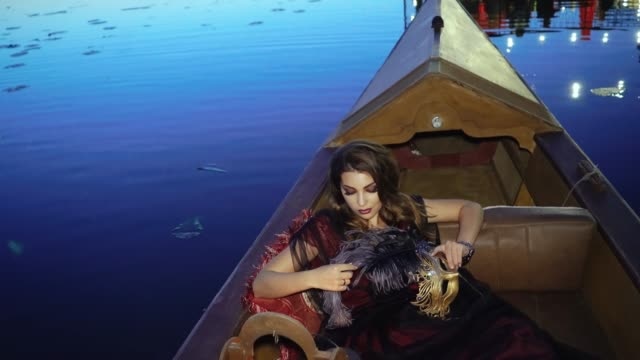A pretty woman is lying in the gondola and stroking a purple feather from a mask in her hands on a blue background on the summer evening. A pretty woman is lying in the gondola and stroking a purple feather from a mask in her hands on a blue background on the summer evening. princess stock videos & royalty-free footage