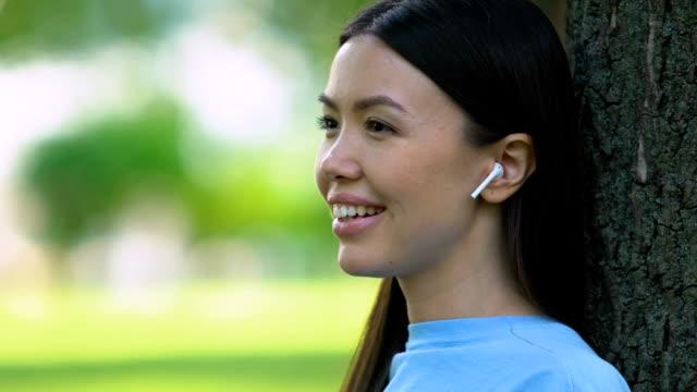 bella donna che ascolta musica attraverso auricolari wireless, rilassandosi nel parco - auricolari wireless video stock e b–roll