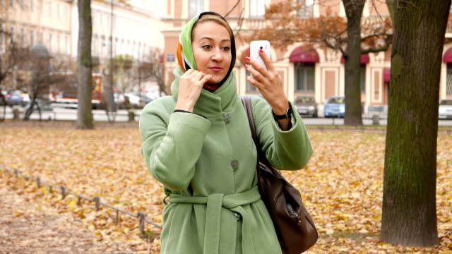 vidéos et rushes de jolie femme regarder les reflets smartphone - étudiant(e)