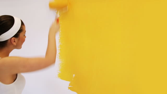 Pretty woman painting Pretty woman painting interior wall of home with paint roller.  yellow stock videos & royalty-free footage