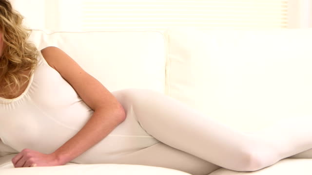 Pretty woman relaxing on couch after yoga medium shot, dolly shot leotard stock videos & royalty-free footage