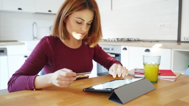 vídeos de stock, filmes e b-roll de compras on-line com o tablet digital uma linda mulher. - pin
