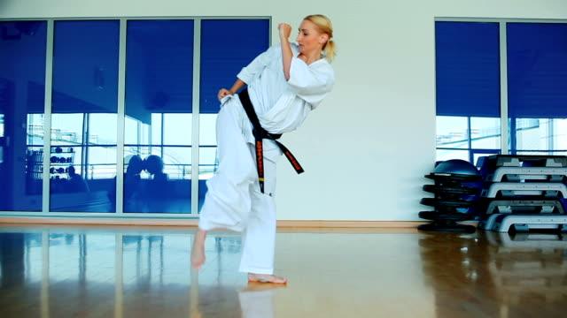 vídeos y material grabado en eventos de stock de mujer bonita muestra un truco de autodefensa en el gimnasio - kárate