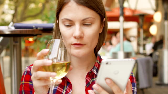 Pretty woman sitting in cafe looking at menu. Female using her cellphone browsing drinking wine video