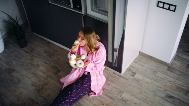 pretty woman sitting on floor in kitchen and eating sweets. satisfied girl - bombolone video stock e b–roll
