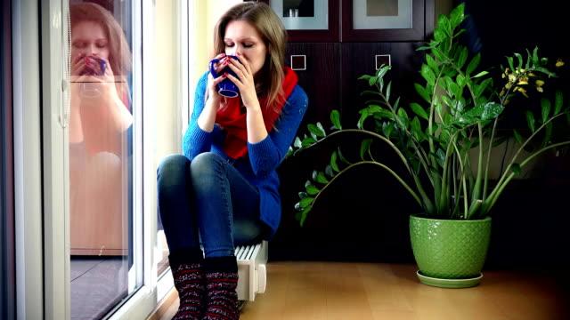 stockvideo's en b-roll-footage met mooie vrouw glimlachen bij camera zittend op de radiator en het drinken van hete thee. - camelia white