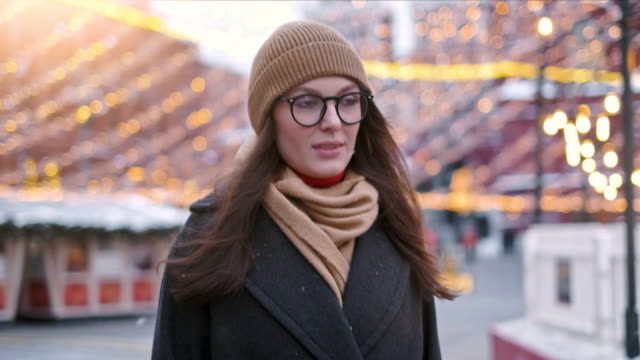 Pretty woman stands on the city square among Christmas decorations and looks straight into the camera
