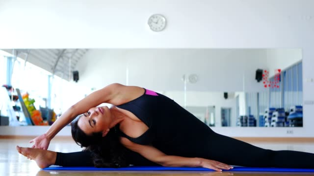 Pretty woman training flexibility in gym on mat video