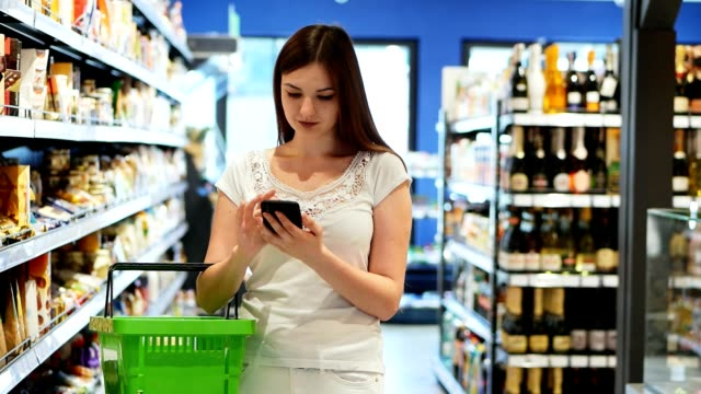 Pretty woman use phone with shopping basket in supermarket, texting sms Pretty woman use phone with shopping basket in supermarket, texting sms, use sale app grocery aisle stock videos & royalty-free footage