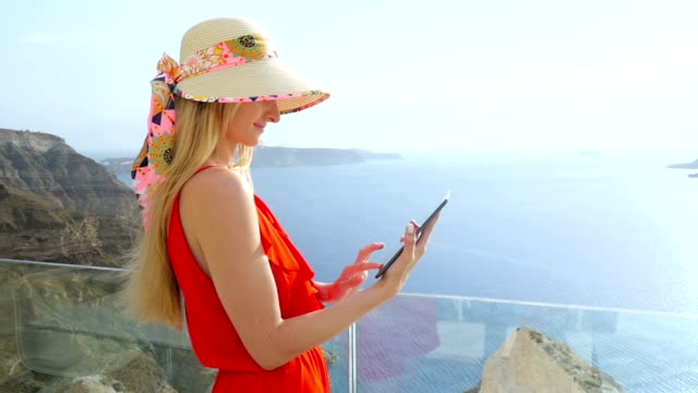 pretty woman using touchpad in santorini - travel agent stock videos and b-roll footage
