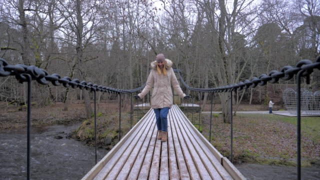 Pretty Woman Walking On Suspension Bridge Begins To Jump On It And Have Fun