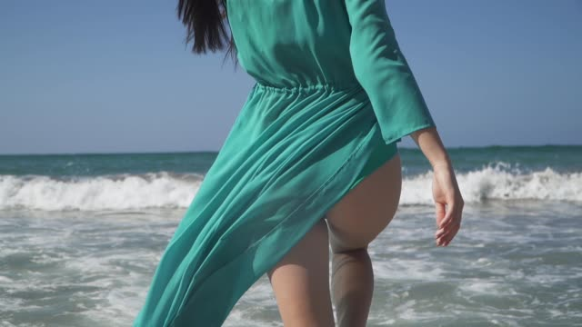 Pretty woman with a perfect body wearing turquoise dress walks into the sea. Dress fluttering in the wind and foaming waves caress beautiful female legs.