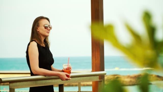 hübsche frau mit cocktail und entspannung in der nähe des meeres. - tropischer cocktail stock-videos und b-roll-filmmaterial