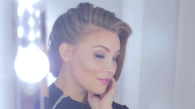Pretty woman with elegant hairstyle looking at her reflection in mirror video