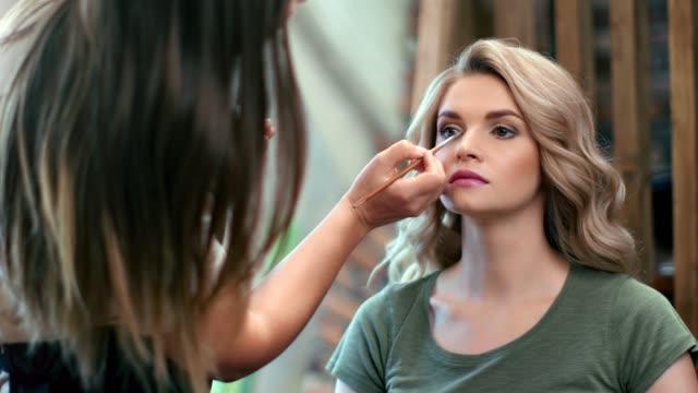vidéos et rushes de jolie femme avec la peau parfaite pendant le travail de maquilleur. plan rapproché moyen vers le haut tiré sur la caméra rouge de 4k - fard à paupières