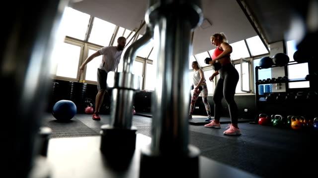 vídeos de stock, filmes e b-roll de mulheres bonitas, exercitando com instrutor na academia - personal trainer