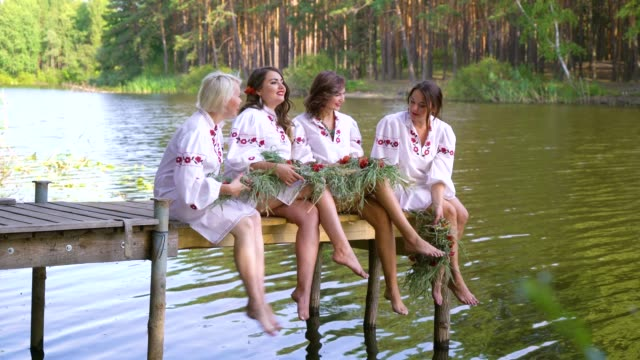 pretty women in ethnic dresses with floral circlets sitting on wooden bridge - славянская культура стоковые видео и кадры b-roll