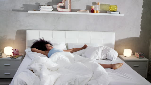pretty young african american woman waking up in bed - sonnecchiare video stock e b–roll