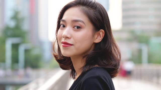 ganska ung asiatisk flicka leende på kamera, slowmotion - kinesiskt ursprung bildbanksvideor och videomaterial från bakom kulisserna