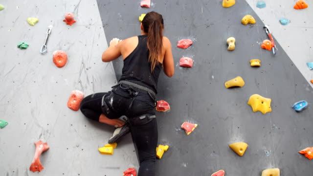 hübsche junge sportliche mädchen klettern auf eine indoor-kletterwand - bouldering stock-videos und b-roll-filmmaterial