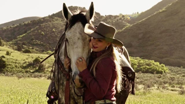 Pretty young blond cowgirl leading her horse Stops To Scratch His Nose Pretty cowgirl leading her horse through a meadow stops to scratch and nuzzle him cowgirl stock videos & royalty-free footage