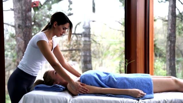 stockvideo's en b-roll-footage met mooie jonge blonde vrouw met een massage in het wellnesscentrum - massagetherapeut