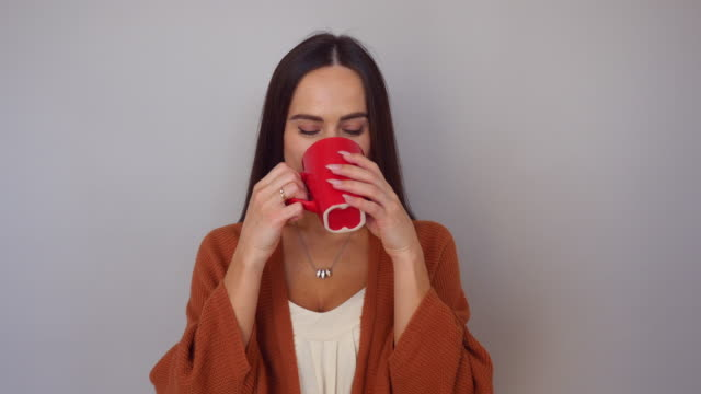 Pretty young Caucasian woman drinking a cup of coffee isolated over white background video